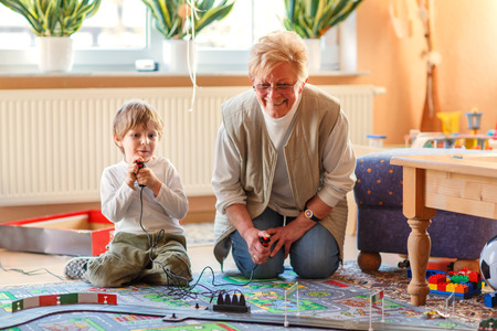 Happy family of two: Grandmother and little grandson playing with racing cars on racetrack, indoors, together. Selective focus on senior woman. Stock Photo