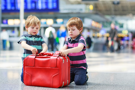 Two little sibling boys having fun and going on vacations trip with suitcase at airport, indoors. photo
