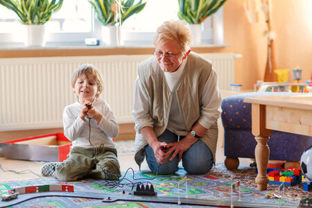 Happy family of two: Grandmother and little grandson playing with racing cars on racetrack, indoors, together. Selective focus on senior woman. photo