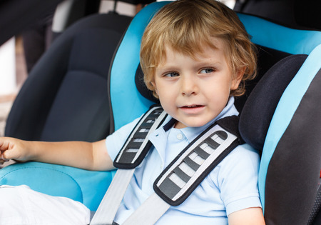 Little boy of 3 years sitting in safety car seat Stock Photo