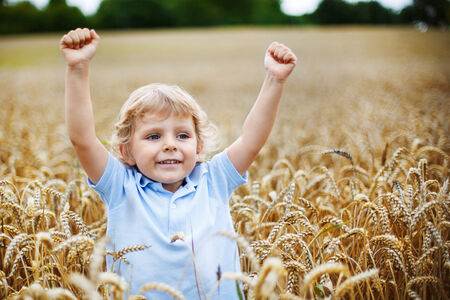 Happy little boy with blond hairs having fun in wheat field in summer, outdoors photo