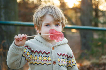 Portrait of beautiful little boy of 2 with big candy, outdoors. Evening light. photo