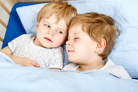 Family Of Two Little Boys Siblings Having Fun In Bed At Home Indoors