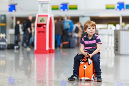 Beautiful blond boy having fun wiht suitcase at airport, indoors. Going on holidays. photo