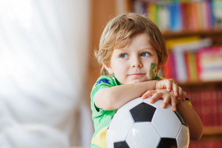 Little blond preschool boy of 4 years with football watching soccer world cup on tv