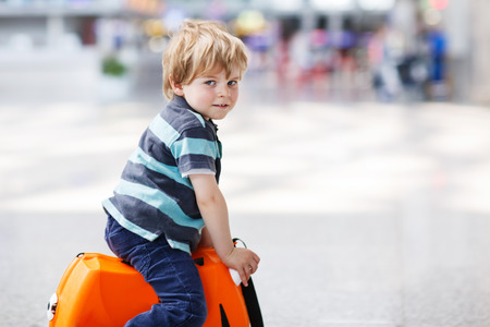 Blond boy of 2 years sitting on suitcase at the airport, indoors and waiting for going on vacations. photo