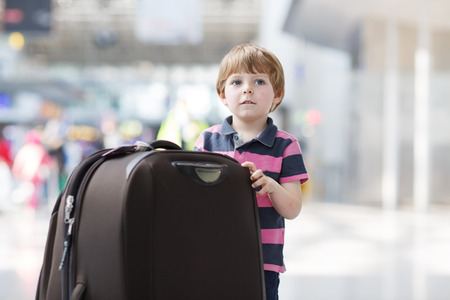 Blond boy of 4 years with huge suitcase at the international airport, indoors and waiting for going on vacations. photo