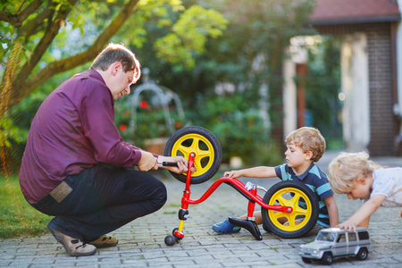Happy family of three person: Two little sibling  boys repairing bicycle wheel with father in summer, outdoors photo
