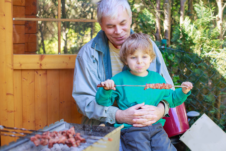 Grandfather and little boy making barbecue and eating grilled meat, outdoors. photo