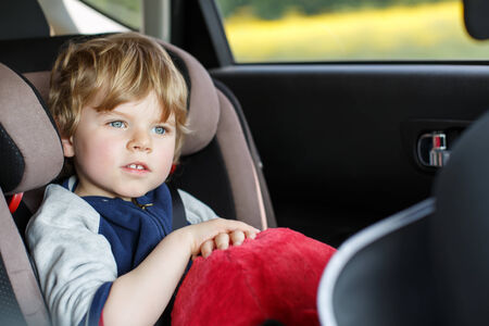 Portrait of little blond boy sitting in safety car seat photo