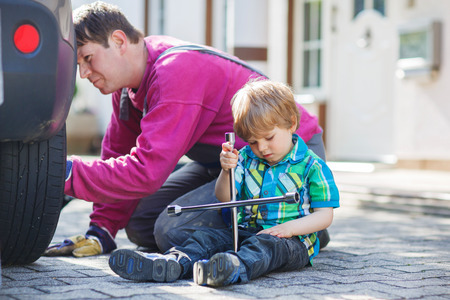 Happy family of two: father and adorable little boy repairing car and changing wheel together on warm day, outdoors. Stock Photo - 28642673
