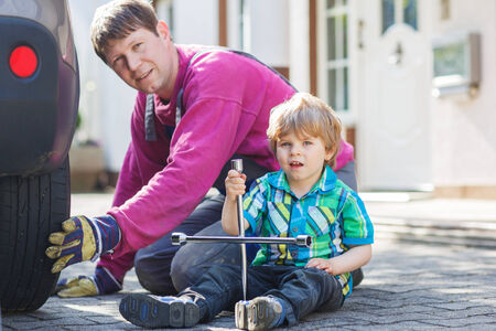 Happy family of two: father and adorable little boy repairing car and changing wheel together on warm day, outdoors. Stock Photo - 28642674