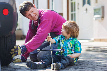 Happy family of two: father and adorable little boy repairing car and changing wheel together on warm day, outdoors. Stock Photo - 28642675