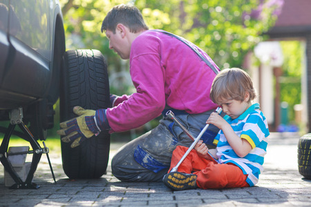 summer tire: Happy family of two: father and adorable little preschool boy repairing car and changing wheel together on warm day, outdoors.