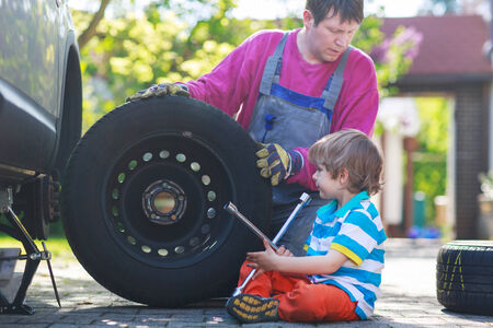 Happy family of two: father and adorable little preschool boy repairing car and changing wheel together on warm day, outdoors. Stock Photo - 28642723