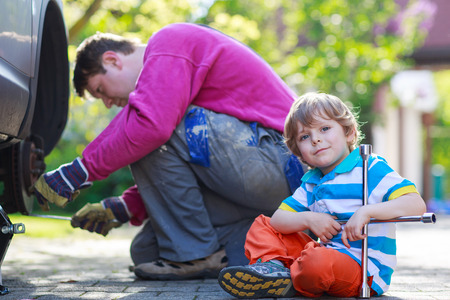Happy family of two: father and adorable little preschool boy repairing car and changing wheel together on warm day, outdoors. Stock Photo - 28642721