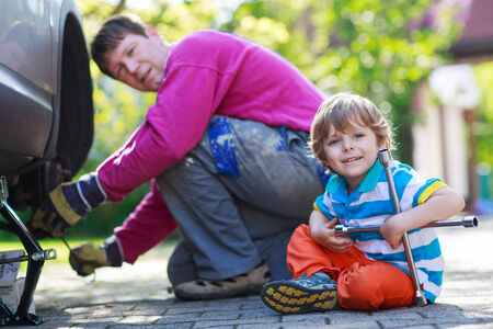 Happy family of two: father and adorable little preschool boy repairing car and changing wheel together on warm day, outdoors. photo