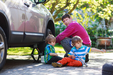 Happy family of three: father and two little boys repairing car and changing wheel together on warm day, outdoors. Stock Photo - 28642789