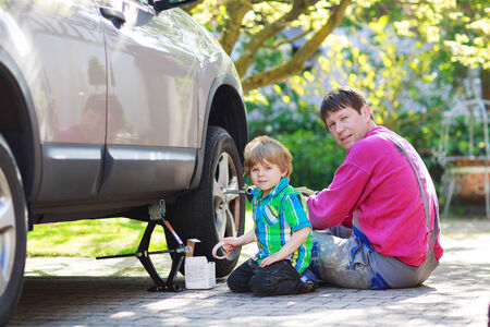 Happy family of two: father and adorable little boy repairing car and changing wheel together on warm day, outdoors. photo