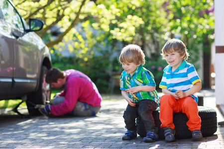 Happy family of three: father repairing car and changing wheel, two little sibling boys sitting on big wheel, outdoors photo