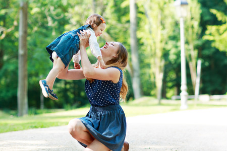 Happy young mother and adorable toddler girl walking through summer park and having fun together, outdoors. photo