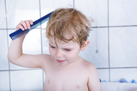 Portrait of lovely little toddler boy of two years after taking bath combing hairs photo