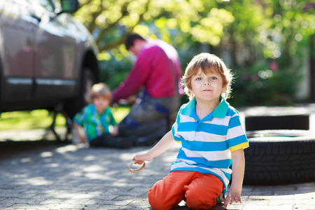 Happy family of three: father and two little boys repairing car and changing wheel together on warm day, outdoors. photo