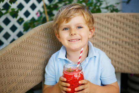 drinking straw: Happy toddler boy drinking healthy selfmade smoothie, watermelon and spinach. Stock Photo