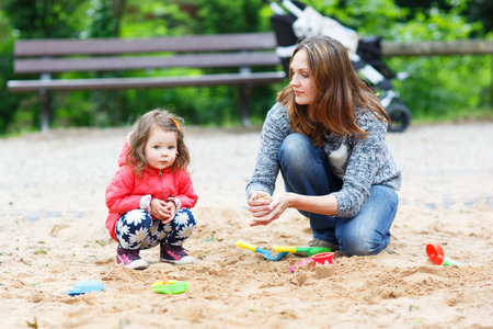 Happy mother and little beautiful daughter playing together on playground in summer photo