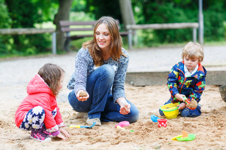 Happy mother and two little children playing together on playground in summer photo