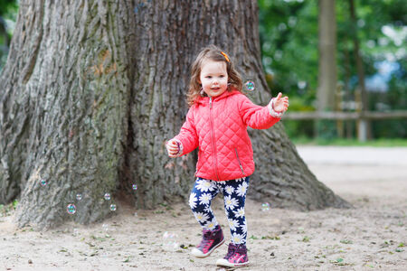 Cute little girl having fun with soap bubbles in summer park photo