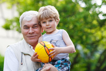 Active grandfather playing with little grandson ball in summer photo