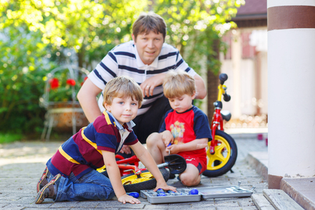 Happy family of three: young father and two little sibling boys reparing broken bicycle, outdoors. Selective focus Stock Photo - 29281560