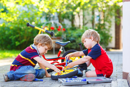 Twins, little boys repairing broken bike, outdoors. Stock Photo - 29281562