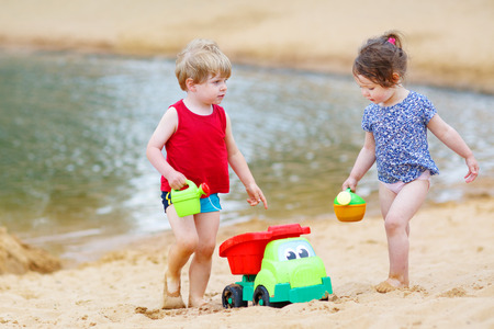 Little toddler boy and girl playing together with sand toys near lake. photo
