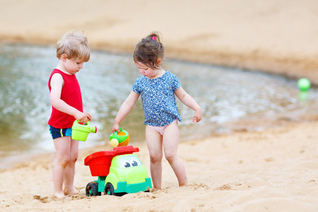 Happy siblings: boy and girl playing together in summer. Stock Photo - 29281563