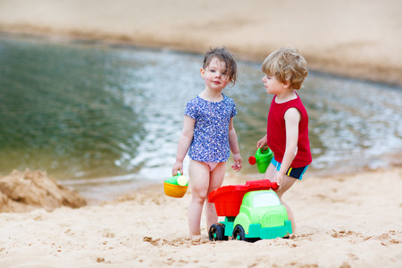 Adorable little toddler friends having fun together on the beach Stock Photo - 29281564