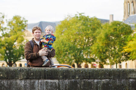 Happy family of two: Adorable little toddler boy and his father in autumn city Stock Photo - 29281565