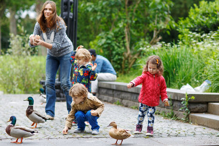 Mother and her children feeding ducks at summer, two little boys and adorable girl photo