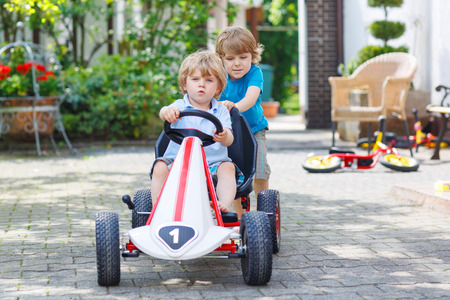 Two happy sibling boys having fun with toy car in summer garden, outdoors. Stock Photo