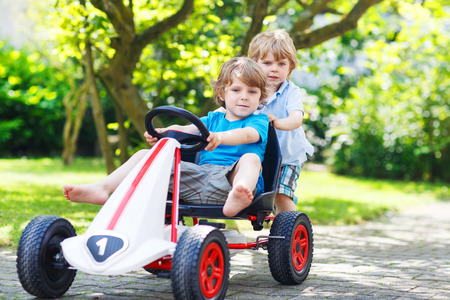 Two happy sibling boys having fun with toy car in summer garden, outdoors. Reklamní fotografie