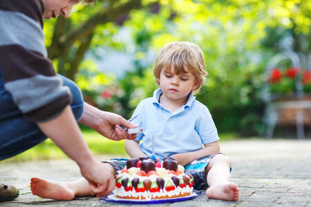 Little adorable boy celebrating his birthday in homes garden with big cake photo