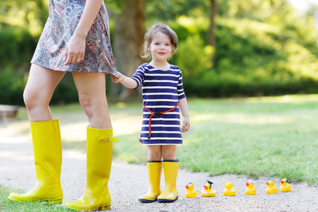 people and nature: Mother and little adorable daughter in yellow rubber boots in summer park
