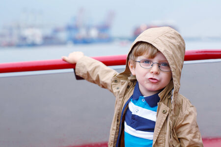 Little boy watching ships on a ferry photo