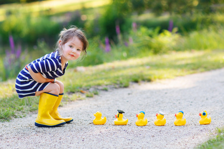 Adorable little girl of 2 playing with yellow rubber ducks in summer park