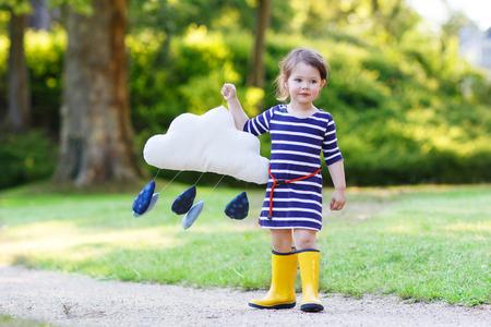 rain boots: Muchacha linda del ni�o en botas de goma de color amarillo con lluvia juguete nube, en verano. Foto de archivo