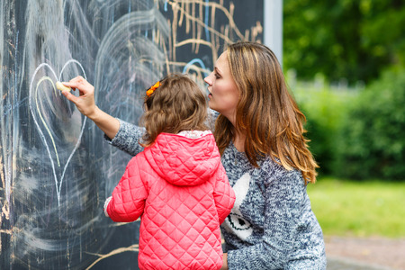Happy mother and little beautiful daughter painting with chalk in park, outdoors photo
