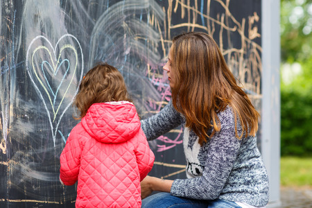 Happy mother and little beautiful daughter drawing with chalk in park, outdoors photo