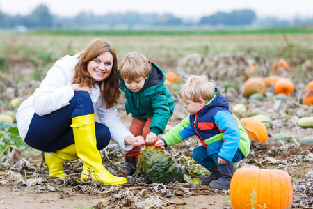 Family of three: Mother and two little siblings gardening on pumpkin patch photo