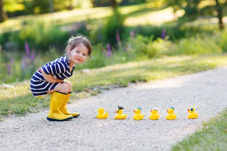 Niña adorable de 2 jugando con los patos de goma amarillos en el parque de verano. Foto de archivo